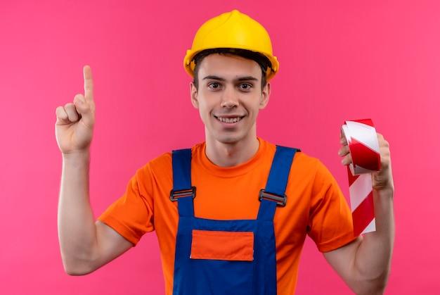 Jeune constructeur homme portant des uniformes de construction et un casque de sécurité pointe le pouce vers le haut et détient un ruban de signalisation rouge-blanc