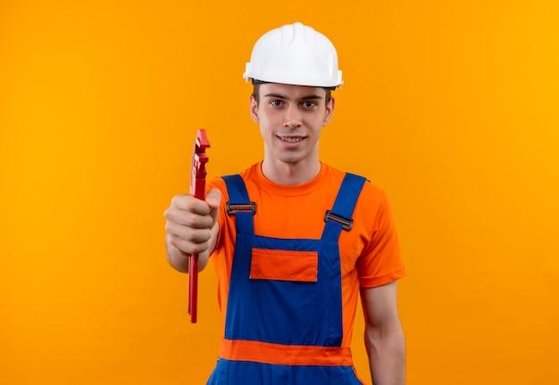Jeune constructeur homme portant des uniformes de construction et un casque de sécurité sourit et détient une pince à rainure