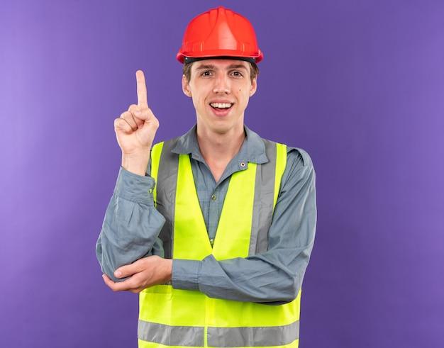 Un jeune constructeur impressionné en uniforme pointe vers le haut isolé sur un mur bleu