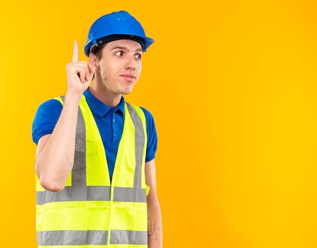 Un jeune constructeur impressionné en uniforme pointe vers le haut isolé sur un mur jaune avec espace pour copie