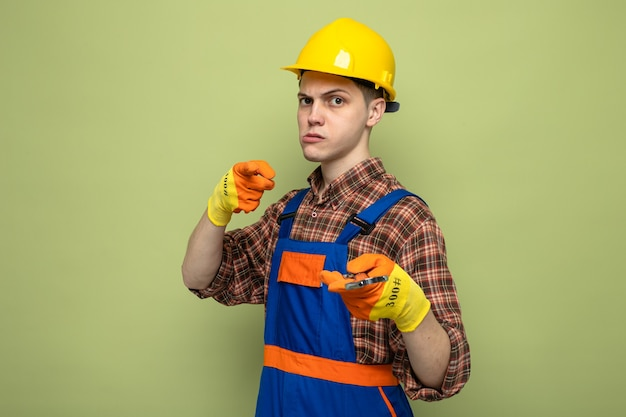 Jeune constructeur masculin confiant en uniforme avec des gants tenant une clé à fourche