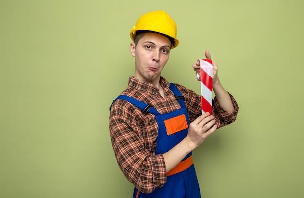 Jeune constructeur masculin impressionné portant l'uniforme tenant du ruban adhésif