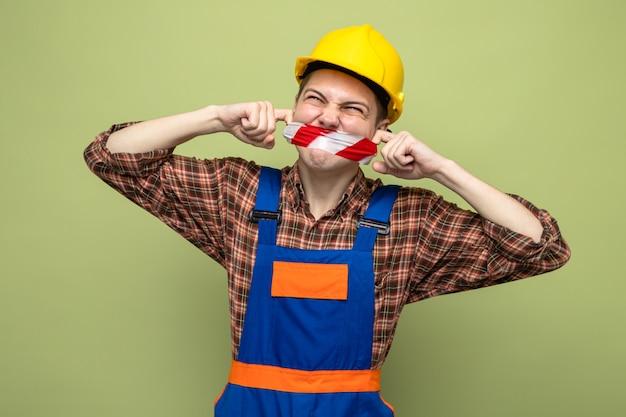 Jeune constructeur masculin portant une bouche scellée uniforme avec du ruban adhésif isolé sur un mur vert olive