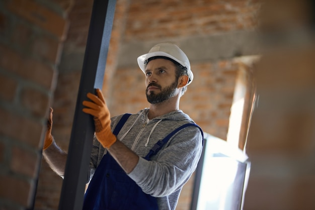 Jeune constructeur masculin portant un casque tenant un goujon métallique pour cloison sèche
