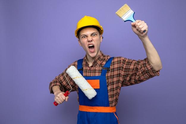 Jeune constructeur masculin portant l'uniforme tenant une brosse à rouleau avec un pinceau isolé sur un mur violet