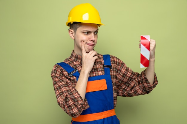 Jeune constructeur masculin portant l'uniforme tenant et regardant du ruban adhésif isolé sur un mur vert olive
