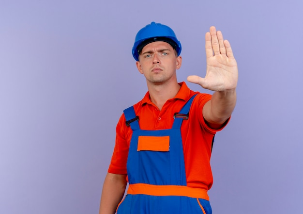 Jeune constructeur masculin strict portant l'uniforme et un casque de sécurité montrant le geste d'arrêt