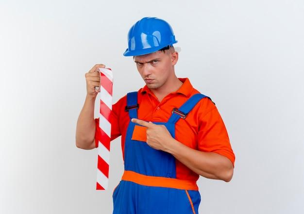 Jeune constructeur masculin strict portant l'uniforme et un casque de sécurité tenant et points à du ruban adhésif sur blanc
