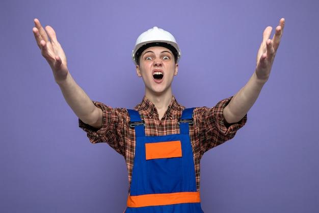 Jeune constructeur masculin en uniforme isolé sur mur violet