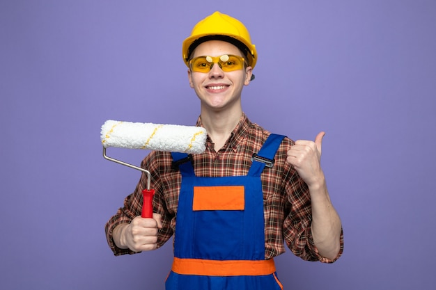 Jeune constructeur masculin en uniforme et lunettes tenant une brosse à rouleau isolée sur un mur violet avec espace de copie