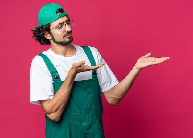 Un jeune constructeur mécontent portant un uniforme avec une casquette faisant semblant de tenir quelque chose