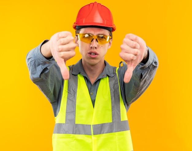 Jeune constructeur mécontent en uniforme portant des lunettes montrant les pouces vers le bas isolé sur un mur jaune
