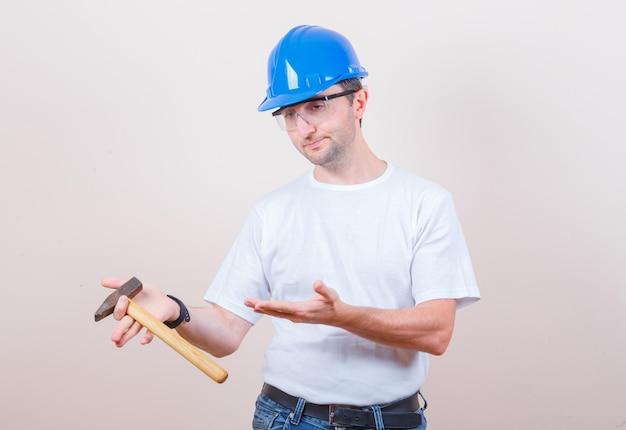 Jeune constructeur montrant un marteau en t-shirt, jeans, casque et pensif