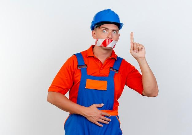 Un jeune constructeur surpris portant un uniforme et un casque de sécurité a scellé sa bouche avec du ruban adhésif et pointe vers le haut