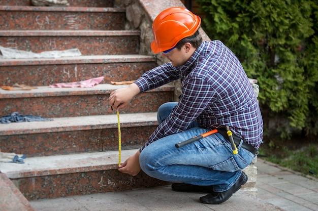 Jeune constructeur vérifiant la hauteur des escaliers par un ruban à mesurer