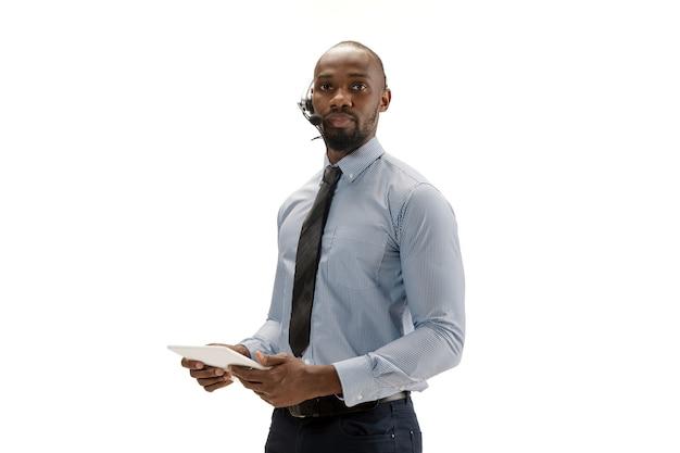 Jeune consultant en centre d'appels afro-américain avec casque isolé sur fond de studio blanc
