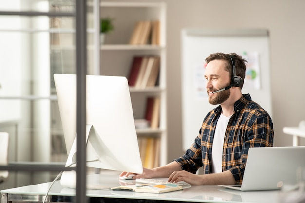 Jeune consultant en ligne occasionnel communiquant avec les clients sur internet tout en regardant l'écran de l'ordinateur par lieu de travail