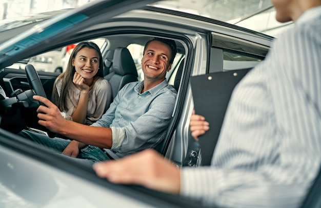 Jeune consultante et acheteurs de couples assis dans un nouveau contrat de signature de voiture au salon de l'auto. concept de location de voiture.