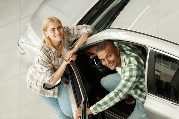 Jeune couple achetant une nouvelle voiture ensemble
