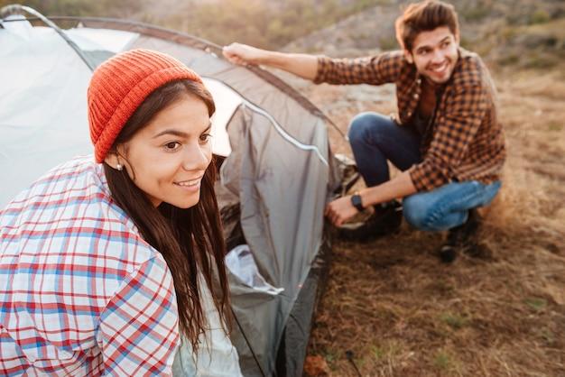 Jeune couple actif la mise en place d'une tente à l'extérieur