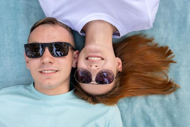 Jeune couple d'adolescents à lunettes portant ensemble sur un tissu bleu bénéficiant de relations amoureuses.