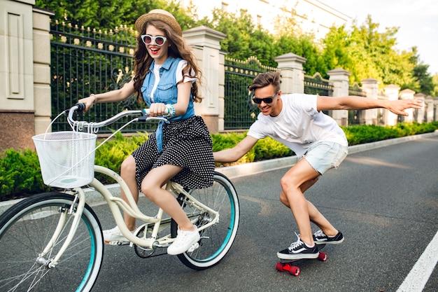 Jeune couple d'adolescents mignons s'amusant l'été sur le coucher du soleil sur la route. jolie fille aux longs cheveux bouclés au chapeau conduisant un vélo, beau mec garde le vélo et monte sur une planche à roulettes.