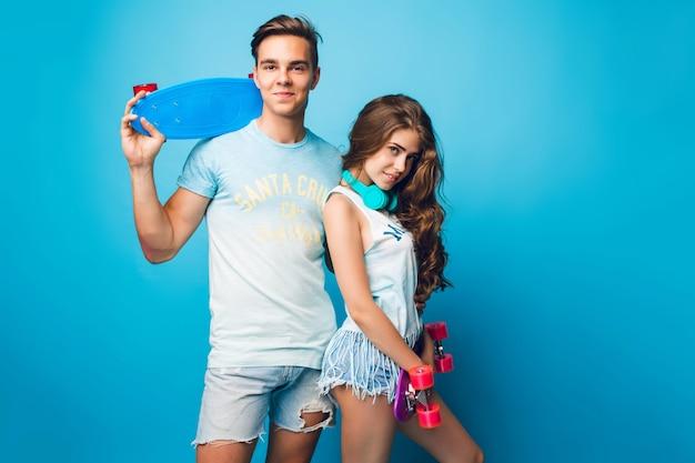 Jeune couple d'adolescents posant sur fond bleu en studio. ils portent des t-shirts, des shorts en jean, tiennent des planches à roulettes et se tournent vers la caméra.