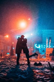 Jeune couple adulte dans les bras de l'autre sur la rue couverte de neige