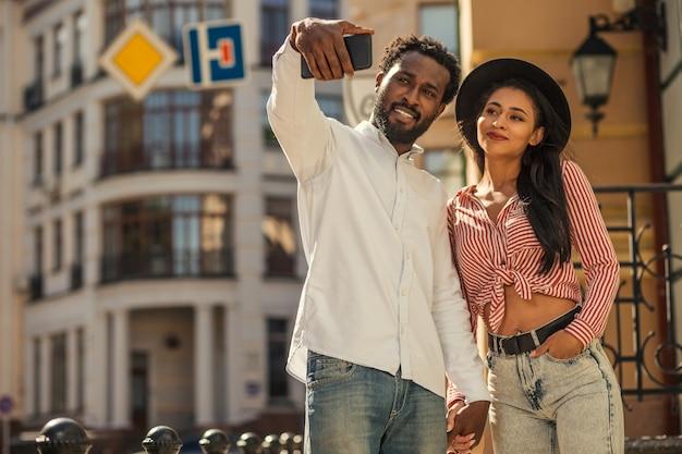 Jeune couple adulte se tenant la main dans la rue et souriant tout en prenant un selfie ensemble