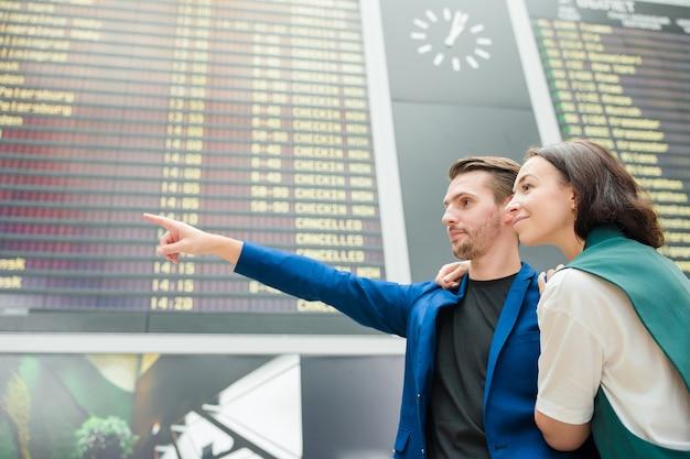 Jeune couple à l'aéroport international en regardant le panneau d'information de vol