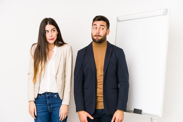 Jeune couple d'affaires caucasien confus, se sent douteux et incertain.