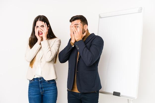 Jeune couple d'affaires caucasien isolé cligner des doigts effrayé et nerveux.