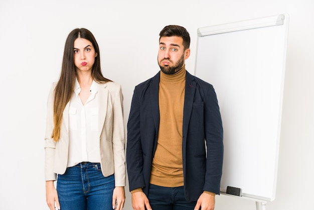 Jeune couple d'affaires caucasien isolé joue les joues, a une expression fatiguée. concept d'expression faciale.