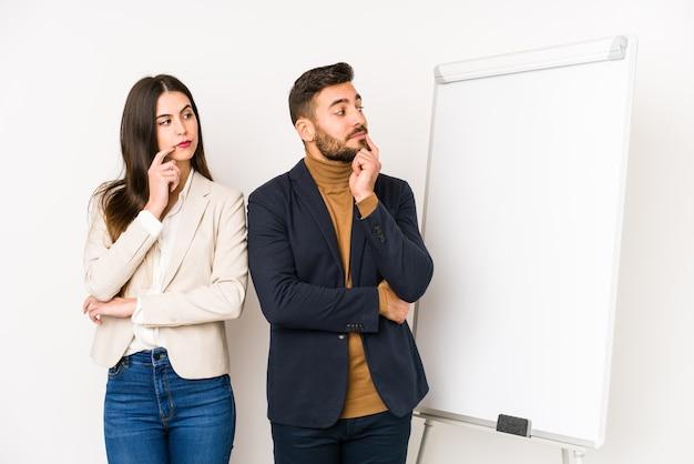Jeune couple d'affaires caucasien isolé à la recherche de côté avec une expression douteuse et sceptique.