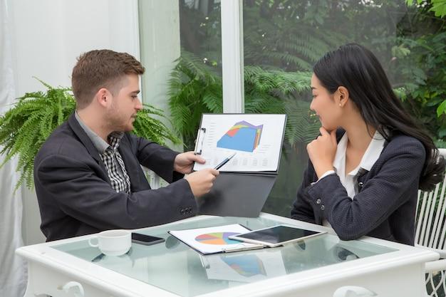 Le jeune couple d'affaires prospère parle et regarde des documents