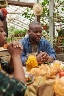 Jeune couple africain assis à table avec de la nourriture et priant les yeux fermés pendant le dîner