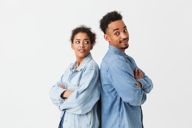 Jeune couple africain en chemises en jean debout dos à l'autre avec les bras croisés sur mur gris