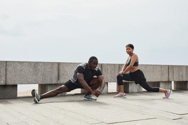 Jeune couple africain faisant des exercices ensemble pendant l'entraînement sportif à l'extérieur