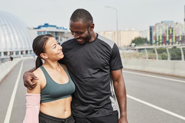 Jeune couple africain souriant et s'embrassant en marchant le long du stade après l'entraînement...