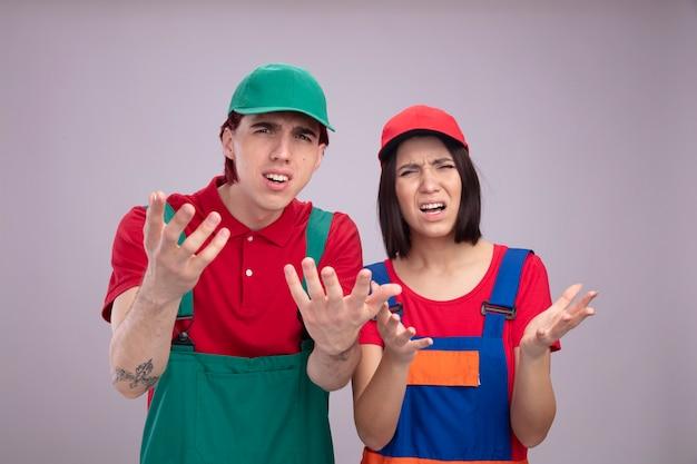 Jeune couple agacé en uniforme de travailleur de la construction et casquette regardant la caméra montrant les mains vides isolées sur le mur blanc