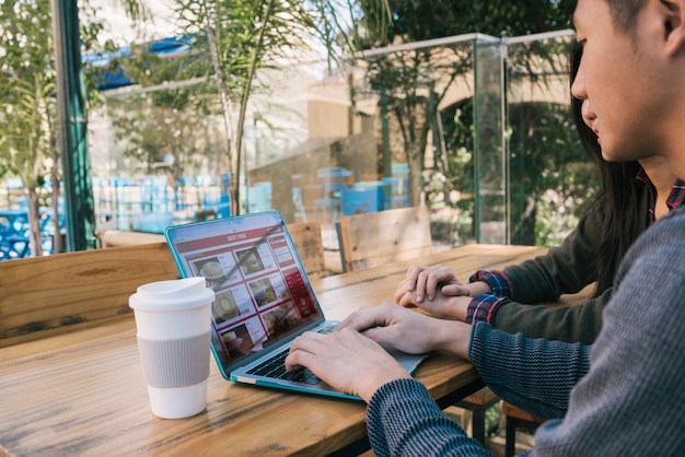Jeune couple à l'aide d'un ordinateur portable au café.