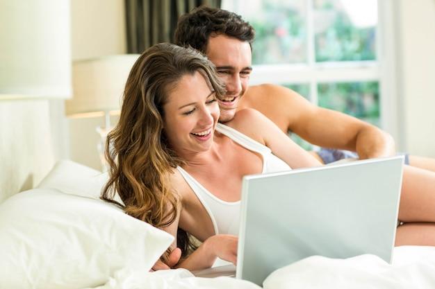 Jeune couple à l'aide d'un ordinateur portable sur le lit dans la chambre