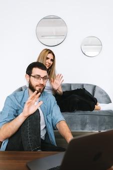 Jeune couple à l'aide d'un ordinateur portable en regardant l'écran du portable sur appel vidéo et salutation avec agitant dans le salon moderne.