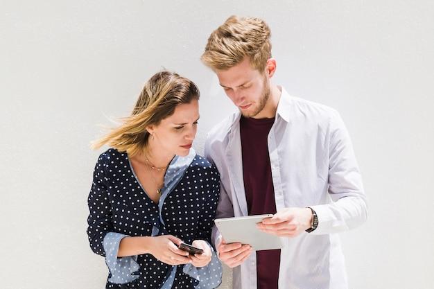 Jeune couple à l'aide de smartphone et tablette numérique