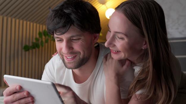 Jeune couple à l'aide de tablette sur le lit dans la chambre tard dans la nuit.