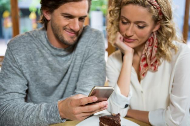 Jeune couple à l'aide de téléphone intelligent à table dans un café
