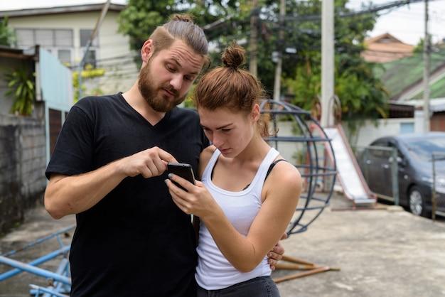 Jeune couple à l'aide de téléphone mobile ensemble dans l'ancienne aire de jeux