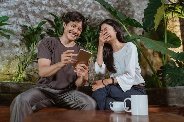 Jeune couple à l'aide de téléphone mobile ensemble à la maison alors qu'il était assis dans le jardin