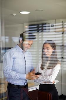 Jeune couple à l'aide de téléphone portable derrière la vitre au bureau