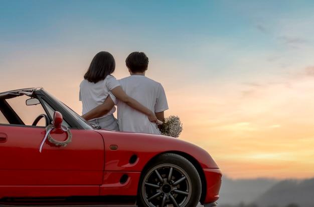 Jeune couple aimant dans un cabriolet au coucher du soleil